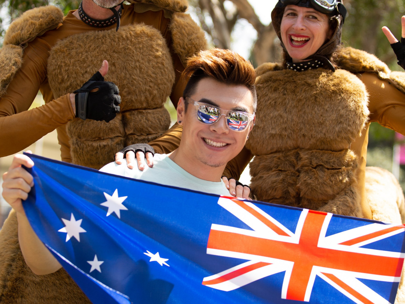 Happy man holding a flag and standing with giant bouncing roos at the Summer Playground in Darling Harbour