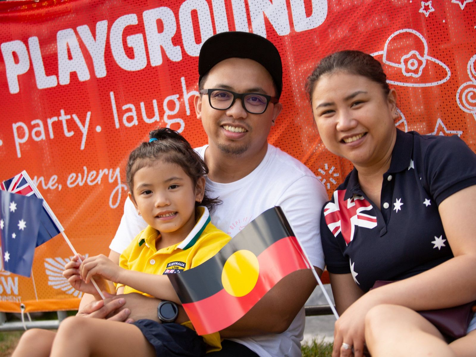Young family holding Australian and Aboriginal flags at the Summer Playground in Darling Harbour