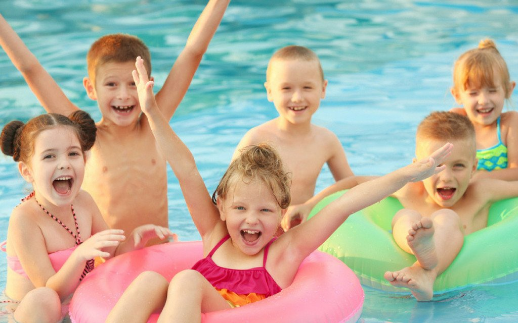 Six happy kids in a pool with two floating donuts